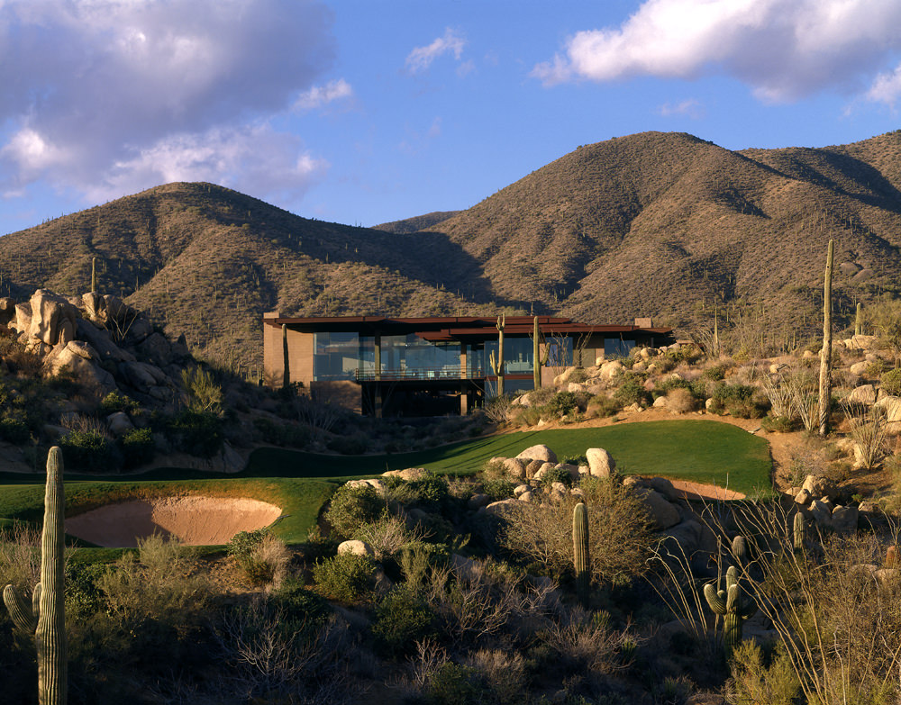 Exterior of Shadow Caster from afar, looking across a putting green at the home that is backdropped by desert mountains.