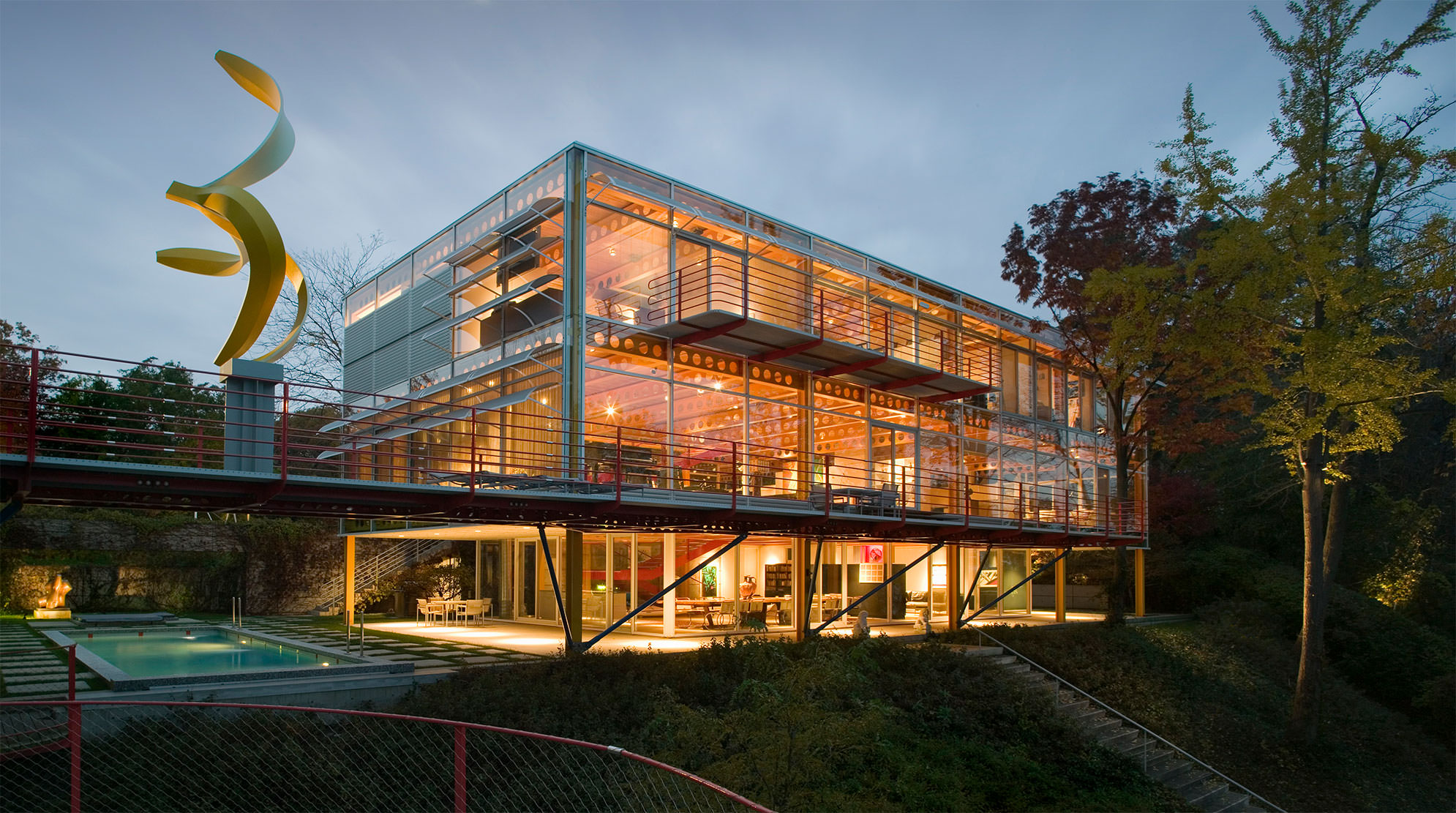 Exterior of Ravine Bluff at night, with the steel-and-glass home aglow with light.