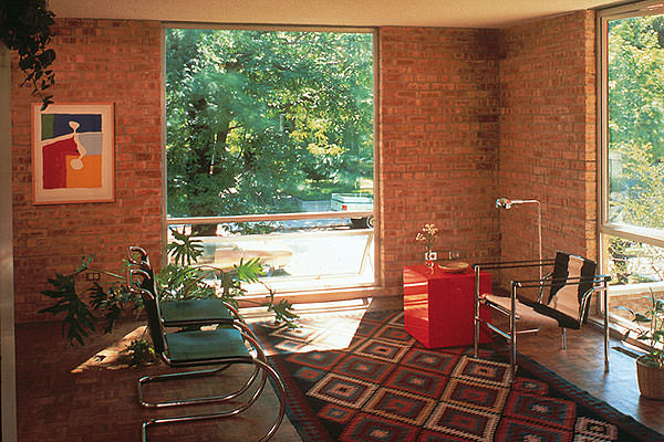 A living room interior with brick walls has large windows that look out to trees.
