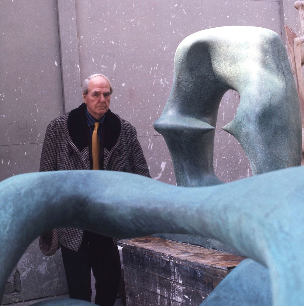Henry Moore, posing beside his sculpture Working Model for Oval with Points