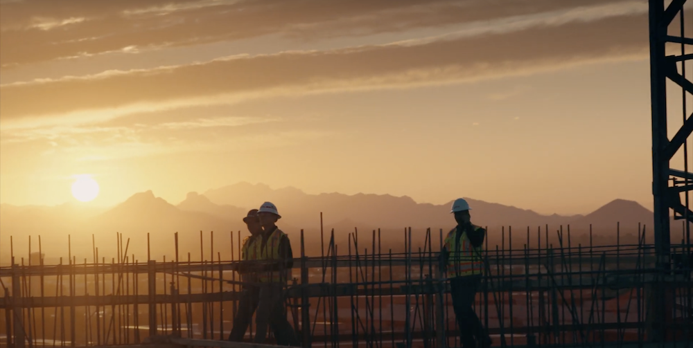 Construction workers on a site overlooking the mountains at sunrise