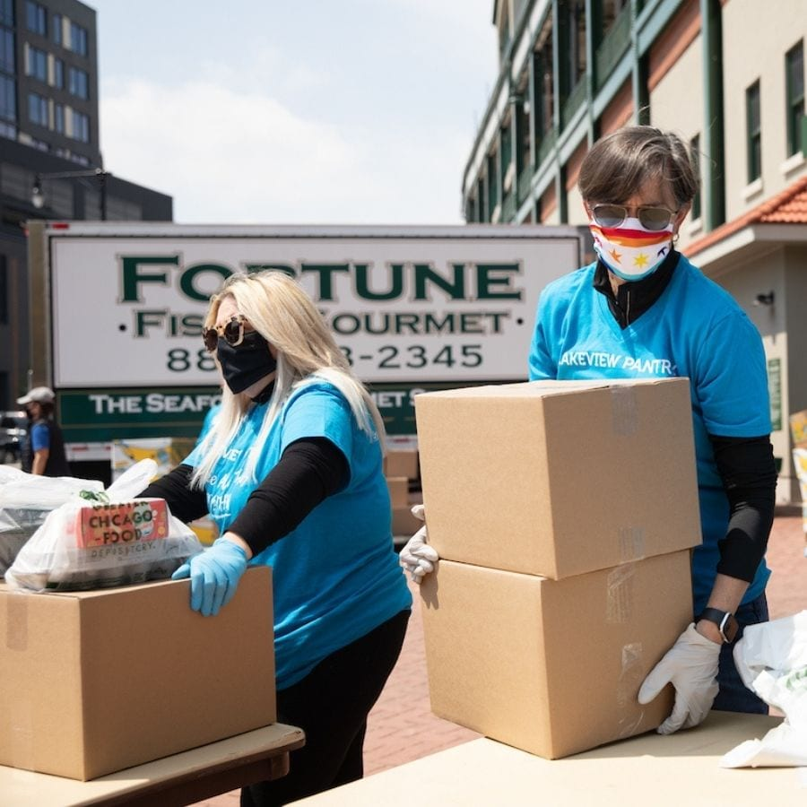 Two volunteers wearing masks lift cardboard boxes of food at Lakeview Pantry