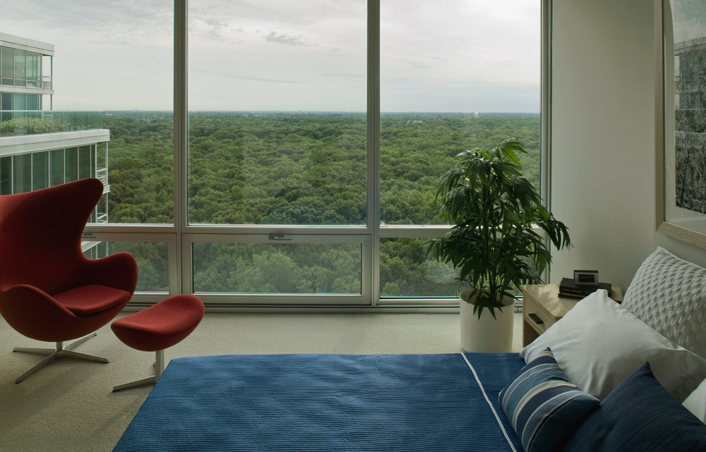 A unit bedroom at Optima Old Orchard Woods. Floor to ceiling glass windows let in an abundance of natural light and show expansive views of nextdoor Harms Forest Preserve