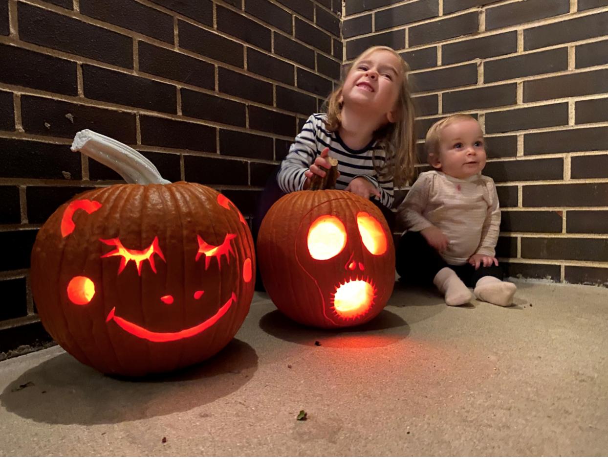 Two kids pose with their jack-o-lanterns