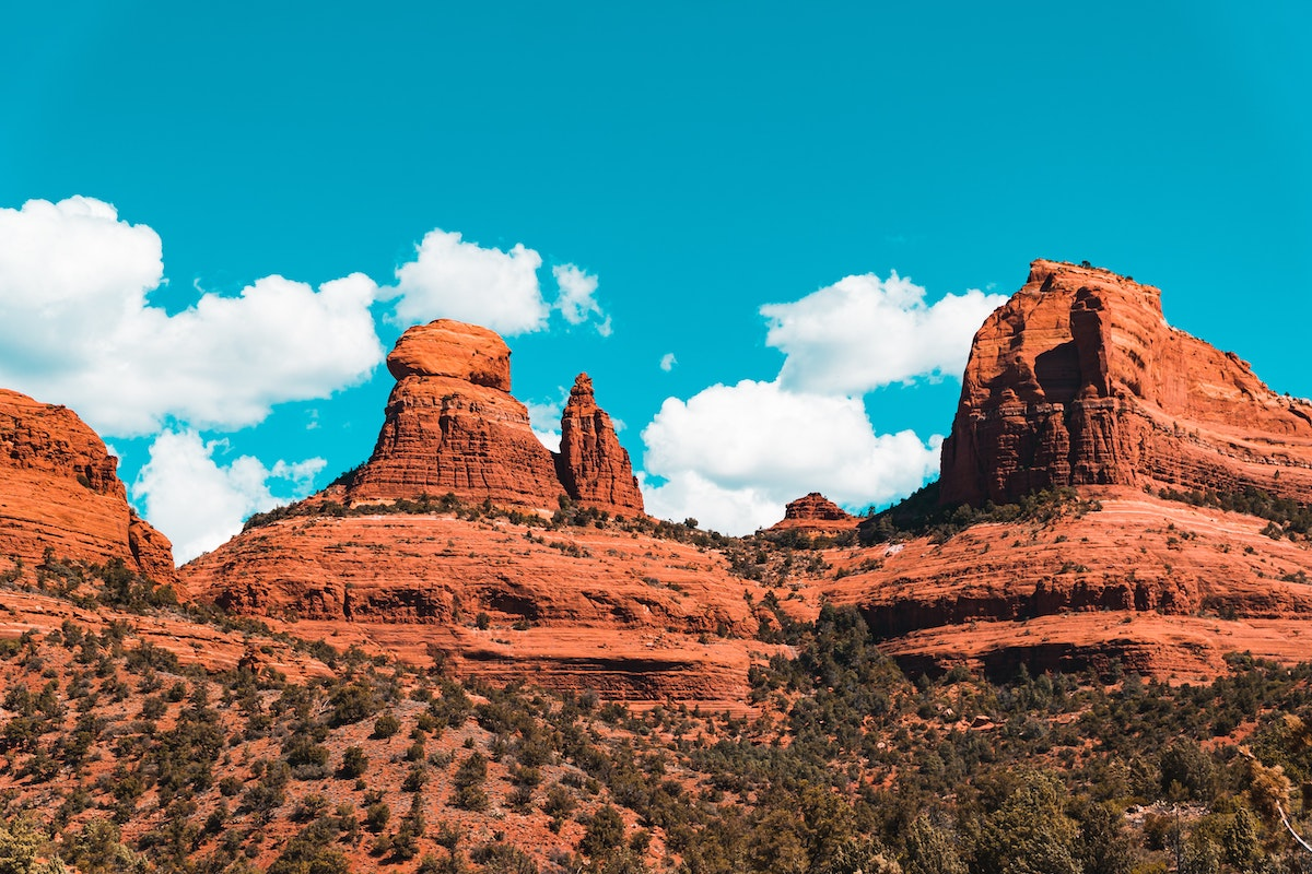 Red rock topography in Sedona, Arizona, contrasted against a bright blue sky
