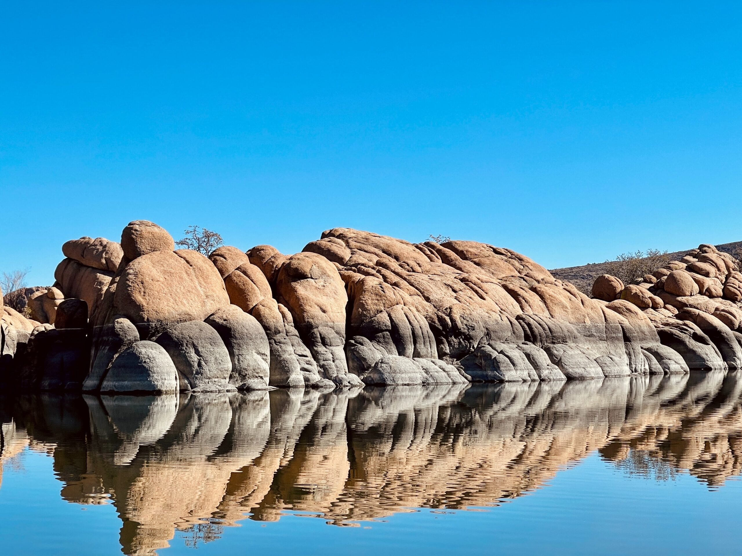 A rock formation reflected in the water at Watson Lake in Prescott, Arizona
