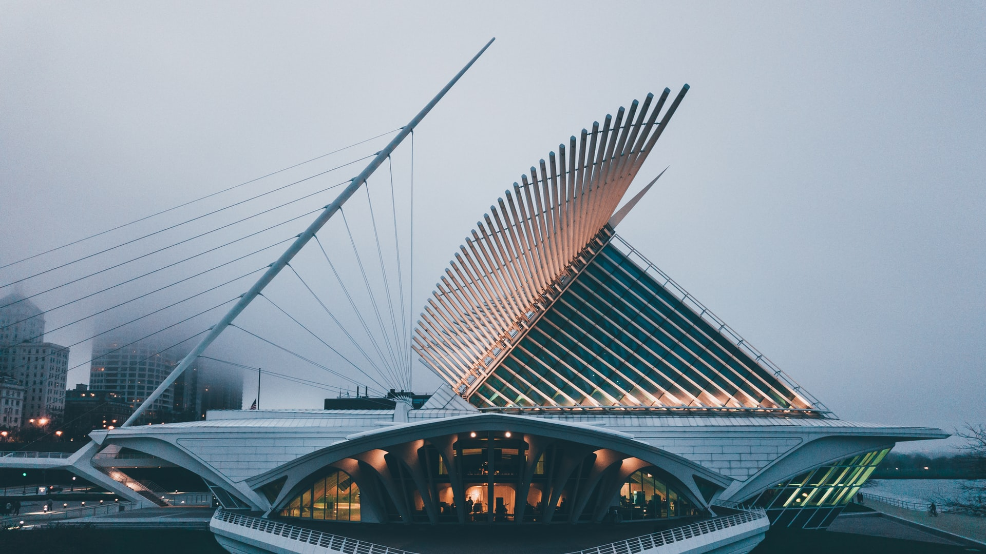 A lit up Milwaukee Art Museum on a foggy day