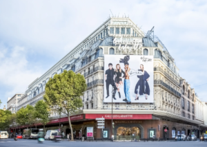 A large white building (Galeries Lafayatte) sits on the corner of two streets. On the front of the building sits an image that seems to be a clothing at for what is inside.
