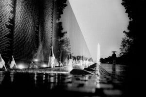 The Vietnam Veterans Memorial is photographed from a low angle in black and white