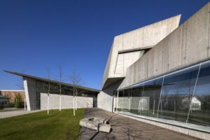 The front of the Vitra Fire Station shows the harsh lines of the concrete structure lined with greenery in its front.
