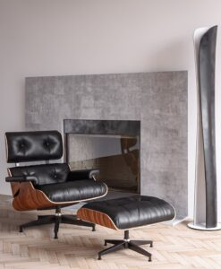 The Eames Lounge Chair sits in front of a marble fire place.