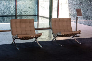 Two Barcelona Chairs sit next to each other in front of glass windows.