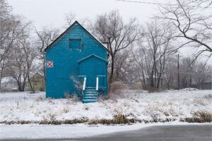 A vibrant blue house is surrounded by leafless trees and a blanket of white snow.