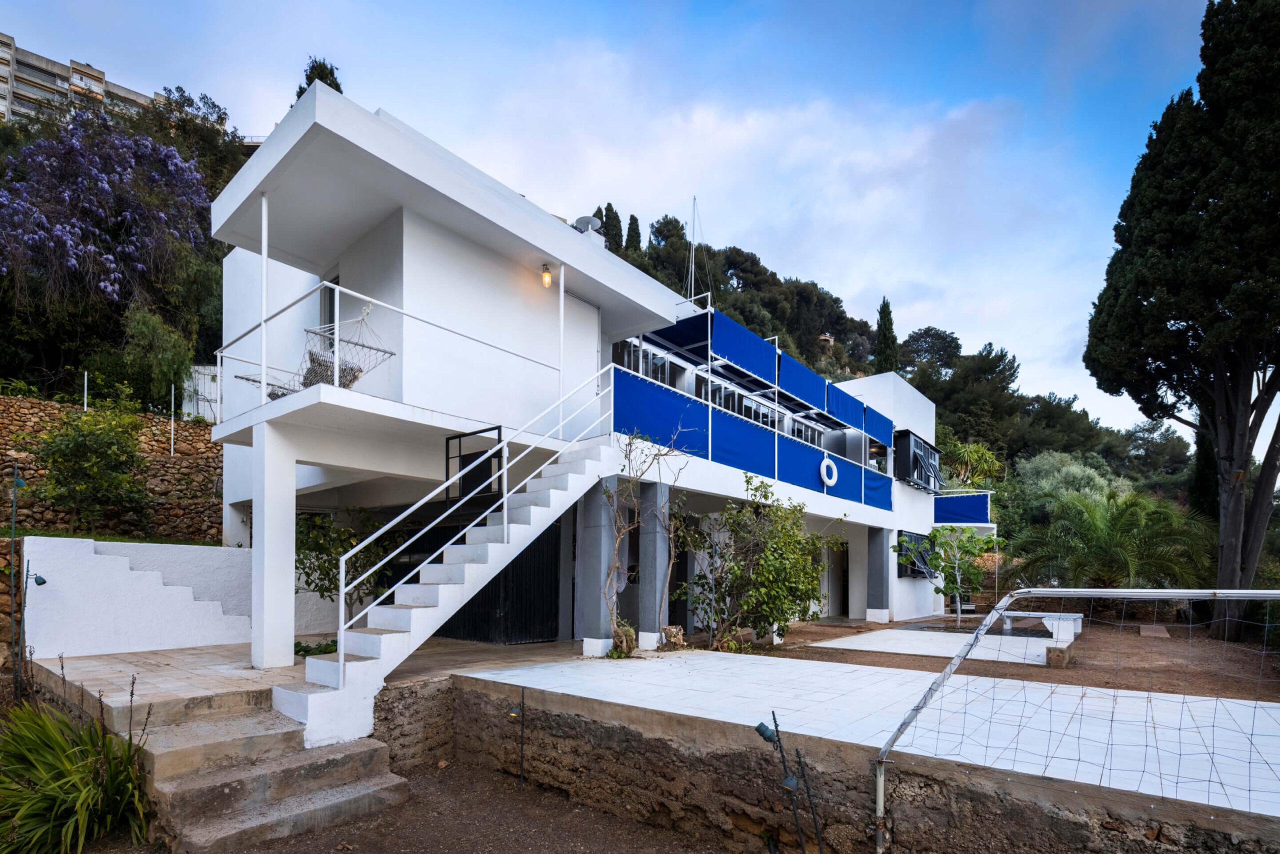 The facade of Eileen Gray's Villa E-1027. The cubist villa is bright white with touches of vibrant blue canvas covering open walkways.