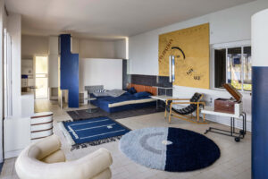A large room is filled with a bed, chairs, rugs, and artwork. All pieces are designed to look like the lived in style of the 1920's.