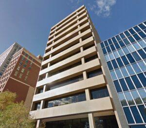 Bright sunlight illuminates the front of a modern designed building.