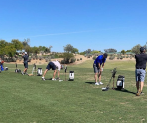 A line of golfers get ready to tee off on a course
