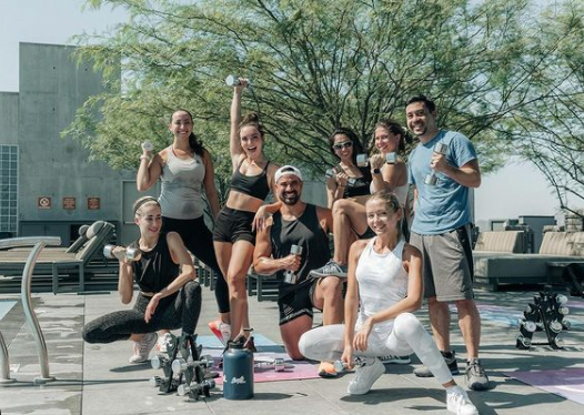 A group of people pose for a picture with exercise equipment